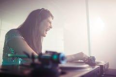 Nätt kvinnlig discjockey som spelar musik arkivbild