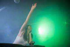 Nätt kvinnlig discjockey som vinkar hennes hand, medan spela musik Royaltyfri Foto