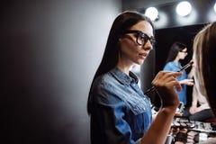 Nätt kvinnlig makeupkonstnär som använder ögonborsten Arkivbild
