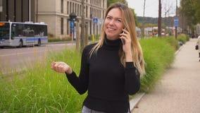 Nätt kvinnlig person som talar vid smartphonen och går nära vägen stock video