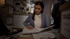 Nätt kvinnlig snut som undersöker sakkunniga rönresultat, dam i polisen, skrivbordsarbete arkivfoton
