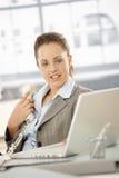 Nätt kvinnlig som i regeringsställning använder telefonen och bärbar dator arkivbilder