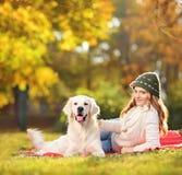 Nätt kvinnlig som ner ligger med hennes labrador retriever hund i PA Royaltyfria Foton