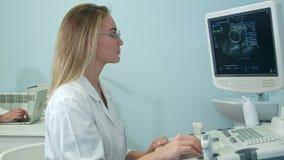 Nätt kvinnlig sonographer som arbetar på ultraljudutrustning arkivfilmer