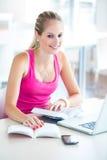 Nätt kvinnlig student med böcker och bärbar dator royaltyfria foton