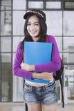 Nätt kvinnlig student som ler på kameran royaltyfri fotografi