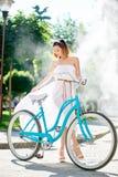 Nätt kvinnligt posera bredvid en cykel framme av en springbrunn Royaltyfri Bild