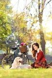 Nätt kvinnligt sitta ner med hennes hund i en parkera Royaltyfri Bild