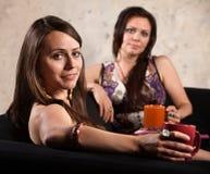 Nätt kvinnor som kopplar av på sofaen Royaltyfri Foto