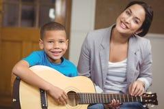 Nätt lärare som ger gitarrkurser till eleven Arkivbild