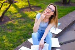 Nätt läsning för den kvinnliga studenten skyler över brister och att le, och studera i vår parkera arkivfoto