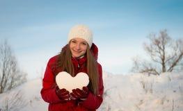 Nätt le flicka som rymmer en hjärta av snö. Förälskelse. Arkivfoto