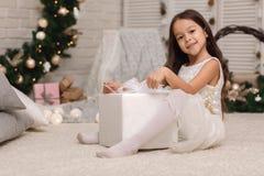 Nätt le flicka som rymmer julgåvan i hand royaltyfri bild
