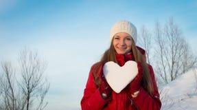 Nätt le flicka som rymmer snöig hjärta. Valentin dag. Arkivbilder