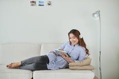 Nätt le hörlurar för kläder för ung kvinna som sitter på soffan och u arkivfoton