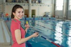 Nätt le instruktörkvinna som rymmer en stoppur på poolside Royaltyfri Fotografi