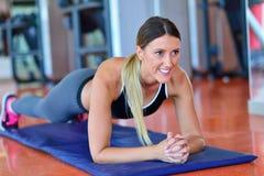 Nätt le konditioninstruktör som gör push-UPS i idrottshallen Ung idrottskvinna som övar på aerobicsgrupp Sjukvård- och viktlo Royaltyfria Bilder