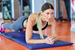 Nätt le konditioninstruktör som gör push-UPS i idrottshallen Ung idrottskvinna som övar på aerobicsgrupp Sjukvård- och viktlo Royaltyfri Bild