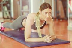 Nätt le konditioninstruktör som gör push-UPS i idrottshallen Ung idrottskvinna som övar på aerobicsgrupp Sjukvård- och viktlo Royaltyfri Foto