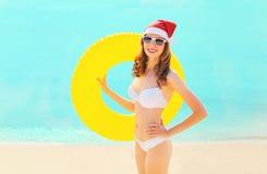 Nätt le kvinna för jul i den röda santa hatten med cirkeluppblåsbar på stranden över havet fotografering för bildbyråer
