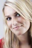 Nätt le kvinna med långt blont hår arkivfoto