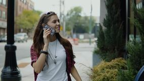 Nätt le kvinna med långt hår som talar på telefonen i staden stock video