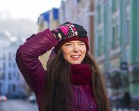 Nätt le lag, hatt och halsduk för vinter för lilor för brunettflicka som bärande går vid den europeiska gatan på vintern Arkivfoton