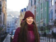 Nätt le lag, hatt och halsduk för vinter för lilor för brunettflicka som bärande går vid den europeiska gatan på vintern Royaltyfri Fotografi