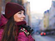 Nätt le lag, hatt och halsduk för vinter för lilor för brunettflicka som bärande går vid den europeiska gatan på vintern Arkivbild