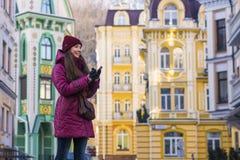 Nätt le lag, hatt och halsduk för vinter för lilor för brunettflicka som bärande går vid den europeiska gatan på vintern Royaltyfria Foton