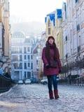 Nätt le lag, hatt och halsduk för vinter för lilor för brunettflicka som bärande går vid den europeiska gatan på vintern Royaltyfri Bild