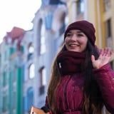 Nätt le lag, hatt och halsduk för vinter för lilor för brunettflicka som bärande går vid den europeiska gatan på vintern Royaltyfria Bilder