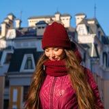 Nätt le lag, hatt och halsduk för vinter för lilor för brunettflicka som bärande går vid den europeiska gatan på vintern Arkivbilder