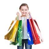 Nätt le liten flicka med shoppingpåsar Royaltyfri Bild