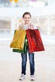 Nätt le liten flicka med shoppingpåsar Arkivfoton