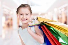 Nätt le liten flicka med shoppingpåsar Royaltyfri Foto