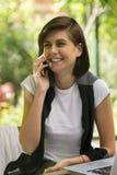 Nätt le ung kvinna som talar på telefonen royaltyfri foto