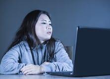 Nätt ledsen asiatisk koreansk studentkvinna som studerar med bärbar datordatoren i spänningen för examenkänsla som borras och fru royaltyfri fotografi