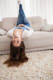 Nätt ligga för brunett som är uppochnervänt på soffan Arkivbilder