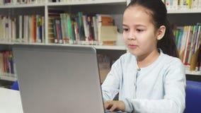 Nätt liten asiatisk flicka som studerar att arbeta på hennes bärbar dator arkivfoton