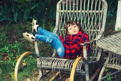 Nätt liten flicka i en stol i trädgården arkivfoton