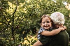 Nätt liten flicka med hennes farfar i trädgård royaltyfria bilder