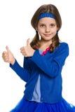 Nätt liten flicka med hennes tummar upp Arkivfoton