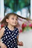 Nätt liten flicka med långa flyghårkörningar arkivbild