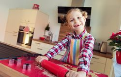 Nätt liten flicka med roliga råttsvansar som gör julkakor Royaltyfria Bilder