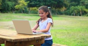 Nätt liten flicka som använder bärbar datordatoren lager videofilmer