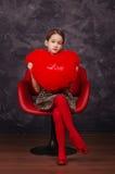 Nätt liten flicka som bär härligt klänningsammanträde i röd fåtölj Hon är hållande flott hjärta i händer härlig för studiokvinna  Fotografering för Bildbyråer