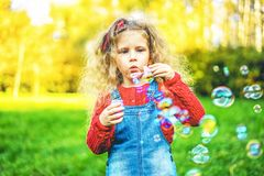 Nätt liten flicka som blåser bubblor i parkera royaltyfri fotografi