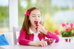Nätt liten flicka som hemma äter hallon Gulligt barn som tycker om hennes sunda nya frukter och bär Arkivbilder