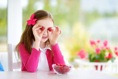 Nätt liten flicka som hemma äter hallon Gulligt barn som tycker om hennes sunda nya frukter och bär Arkivbild